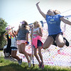 BRYAN EATON/Staff photo. Girls jump up to have their image frozen at the photo booth at the Boys and Girls Club carnival on Thursday afternoon, an annual year-end event. The club is open next week, but won't be that busy as some youngsters head back to school.