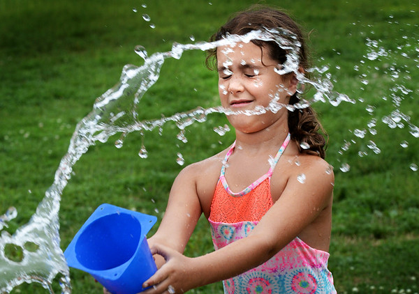 BRYAN EATON/Staff photo. Lilly Voltero, 8, reacts as she gets he by a spray of water at the Boys and Girls Club on Tuesday afternoon. First and second-graders were playing water games, this one with each partner throwing water from five-gallon buckets, whoever empties theirs first, wins.