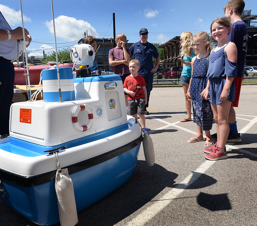 """BRYAN EATON/Staff photo. Youngsters get a kick out of """"Coastie"""" a talking boat the dispenses humor with water saftey tips at USCG Station Merrimack's open house."""