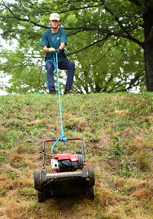 BRYAN EATON/Staff photo. Harry Spaulding, pictured, and Noah Menin, gain upper body strength by lowering and lifting a lawnmower with a rope on the sloping landscape at the Bartlet Mall in Newburyport on Wednesday morning. The two college students, both from Newburyport, are summer workers at the Parks Department.