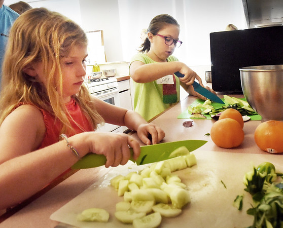 BRYAN EATON/Staff photo. Emma Beard, left, and Josie Ciccone, both 9, learn to slice and dice as they put together a cucumber salad in the nutrition room at Newburyport HIgh School on Tuesday. They were learning about international cooking in the Newburyport Youth Services Summer Program this week with Tuesday's theme being food from the Mediterranean area.