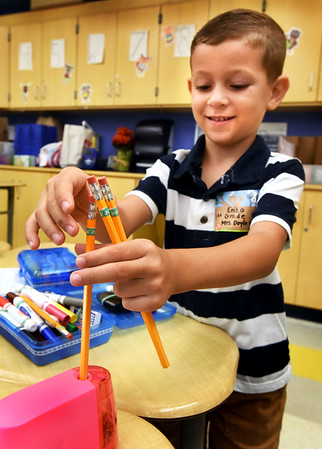 BRYAN EATON/Staff photo. Bresnahan School first-grader Enzo Lemes, 5, gets busy sharpening his pencils while waiting for class to start.