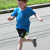 JIM VAIKNORAS/Staff photo Bayne Desmond, 4, of Kensington, runs while wearing a shark hat on High Street in the Yankee Homecoming Parade Sunday. He was marching with KB Center of Dance and Movement.
