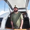 BRYAN EATON/Staff photo. Donning a captain's hat, Opportunity Works client Travis Dickens takes the wheel of the Impossible Dream for a spell.
