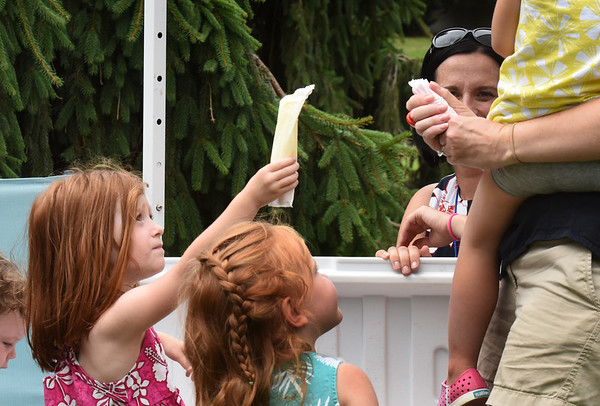 BRYAN EATON/Staff photo. Emilia Wright, 4, left, helps her mother Jessica hand out popsicles at the Greater Newburyport Mothers and Families Club information booth.