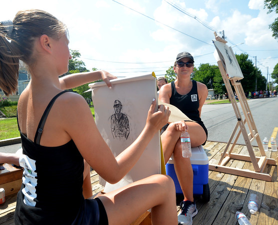 JIM VAIKNORAS/Staff photo Hollis Elorott sketches her mom Lisa as they ride on the Newburyport Art Association float on High Street in the Yankee Homecoming Parade Sunday.