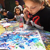 BRYAN EATON/Staff photo. Avery Russell, 7, blows bubbles into different colored paint creating different patterns at Colorful Kids Art Studio owned by Renee Schneider at the Cedar Street Studios in Amesbury. The youngsters were creating the background for an under sea work of art in the weeklong course run by the department of Newburyport Youth Services.