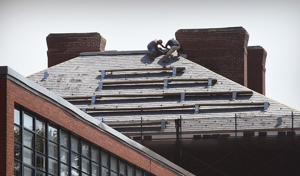 BRYAN EATON/Staff photo. Jobs that are made tougher in extreme heat include lifeguards, officers working traffic details and bakers. Roofers must not be left out of that list like these on the roof of the Spalding School in Salisbury which is being turned into affordable housing.