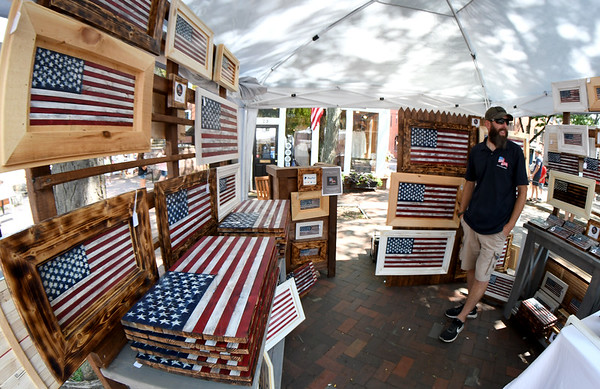 JIM VAIKNORAS/Staff photo Woodworker Jeffery McKenzie sells flags painted on reclaimed wood  during Yankee Homecoming Tuesday.