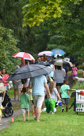 JIM VAIKNORAS/Staff photo People donned umbrellas and rain gear as they check out the booths  in the rain at Family Day at Maudslay Saturday.