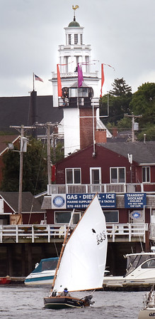 BRYAN EATON/Staff photo. A sailboat  passes under the Range Light and the Old South Church heading down the Merrimack River on Tuesday afternoon. The sailor did some maneuvering as he was with the tide, but fighting the wind from the northeast.
