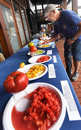 BRYAN EATON/Staff photo. Marty Silvia, Kensington, N.H. tastes a Lucky Tiger at the tomato tasting at Newburyport's Farmers' Market on Sunday. Tasters got to sample the various locally berries, learn about them and different dishes made with them.