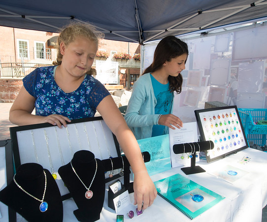 JIM VAIKNORAS/Staff photo Taryn Lebreck and Tessa Porter, both 12, sell hand made jewelry and elephant art prints at the on Inn Street during Yankee Homecoming Tuesday. The girls are students at the River Valley Charter School, $5 of every purchase goes to charities to help African elephants.