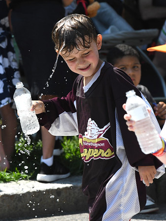 JIM VAIKNORAS/Staff photo Dylan Arel of Newburyport pours water on his head to cool off on High Street in the Yankee Homecoming Parade Sunday.
