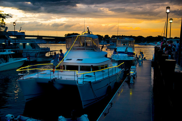 JIM VAIKNORAS/Staff photo Boats decorated with lights sit in the embayment at Market Landing Park in Newburyport as the sunset paints clouds from a clearing thunderstorm Thursday night.