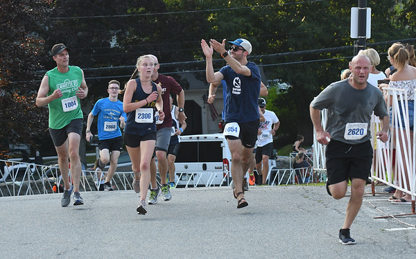 JIM VAIKNORAS/Staff photo  Runners in the 5k make their way up the road to Newburyport High School in the Newburyport Lions Club Yankee Homecoming Road Race.