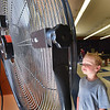BRYAN EATON/Staff photo. Sean Choquette, 7, of Amesbury stops by to cool off in front of giant fans in the game room of the Boys and Girls Club in Salisbury as they moved activities indoors. Most will likely be held inside Tuesday and Wednesday as the temperatures climb into the mid-90's with humid air.