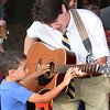 BRYAN EATON/Staff photo. Rowan Alphonse, 5, strums music teacher Gardner Rulon-Miller's guitar as he welcomed students to the first day of classes at the Bresnahan School with song.