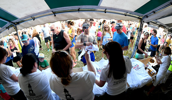 JIM VAIKNORAS/Staff photo Volunteers give out shirts at registration at the Newburyport Lions Club Yankee Homecoming Road Race.