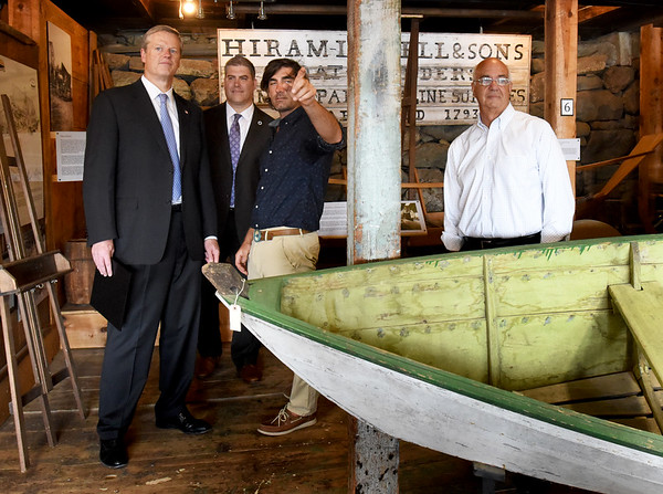 BRYAN EATON/Staff photo. Governor Charlie Baker, left, listens to Graham McKay of Lowell's Boat Shop in Amesbury talk about the history of the place with Rep. Jim Kelcourse and Amesbury Mayor Ken Gray, right.
