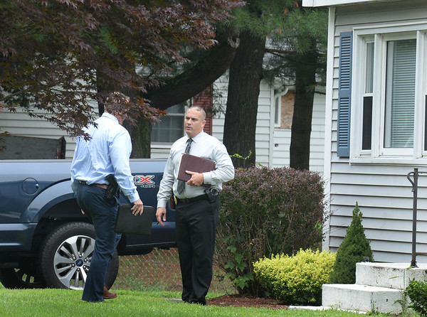 BRYAN EATON/Staff photo. Authorities including Salisbury Police Detective Keith Forget, right, look to talk to neighbors.