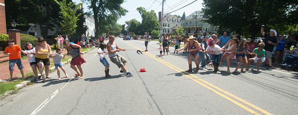 JIM VAIKNORAS/Staff photo The Pond Street Irregulars, a group of locals who attend the parade every year, play tug of war on High Street during a lull in the Yankee Homecoming Parade Sunday.