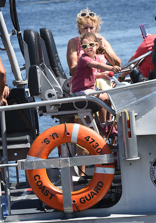BRYAN EATON/Staff photo. Sara Zeid, 3, of Newburyport checks out the wheel on one of the U.S. Coast Guards motor lifeboats during Station Merrimack's open house. She was there with her brother, George, 2, and grandmother Diane Xenelis, of Newburyport, pictured behind.