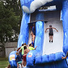 BRYAN EATON/Staff photo. Youngsters play on a giant waterslide at the Boys and Girls Club in Salisbury, one of several water activities to cool off with during the heat.