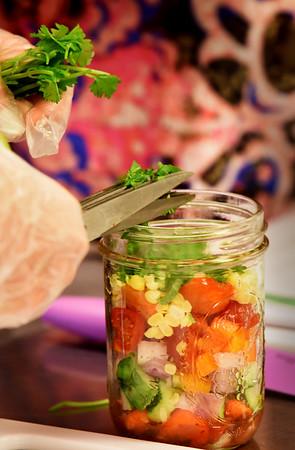 BRYAN EATON/Staff photo. Lehane uses herb shears to cut cilantro into the Southwestern corn Mason jar salad.