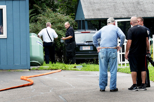 BRYAN EATON/Staff photo. Amesbury police and fire responded to a propane tank that was hit by a car on the side of a residential garage on Haverhill Road across from Hodgie's Ice Cream late Tuesday morning. No injuries were reported, though traffic was down to one lane during the investigation. The building inspector was called to the scene.