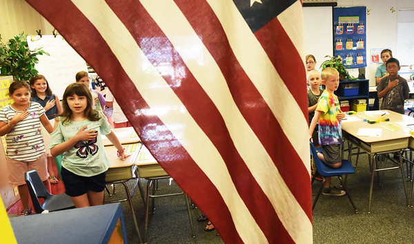 BRYAN EATON/Staff photo. Amesbury Elementary School third-graders say the Pledge of Allegiance on the first day of classes, led by principal Walter Helliesen over the intercom. He leads on the first and last day of school with students taking turns throughout the year.