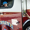 BRYAN EATON/Staff photo. Levi Tibbetts, 4, of Newburyport has his photo taken by his mother, Andreya, as he takes his turn sitting in a Newburyport fire engine. The department did a demonstration on fire safety at the Emma Andrews Library and Community Center late Thursday morning then gave younsters a tour of the equipment on the engine.