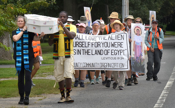 BRYAN EATON/Staff Photo. A group of religious and faith-based individuals march along High Road in Newbury carrying a white coffin protesting the detention of children by I.C.E.