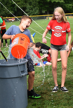 BRYAN EATON/Staff Photo. Landon Theberge, 10, Amesbury hands a bucket of water with holes in it to Morgan Weaver, 11, of Salisbury as their team moves it down the line at the Boys and Girls Club on Wednesday afternoon. It's Splish Splash week and they were playing Holey Bucket Relay where the water is transferred from one bucket to another and the bucket at the end of the line wins for the team.