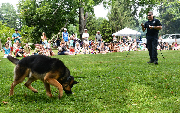 BRYAN EATON/Staff Photo. Essex County Sheriff Department's Captain Thomas Cote and Dash give a demonstration on tracking with smell at Kids Day in the Park as the canine finds the mark.