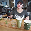 BRYAN EATON/Staff Photo. Changing Tides Cafe manager Michelle Diaz shows off the different compostable cups they use to keep plastic of the landfill. The clear ones for for cold drinks, the others for hot.