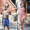 BRYAN EATON/Staff Photo. Wyatt Hanson, 3, left, and sister Elsa, 5, of West Newbury get a kick out of the streams of water shooting up at the water fountain on Inn Street in Newburyport, but are reluctant to run through them on Monday afternoon. It's the last week of summer fun for Elsa as she starts kindergarten next Wednesday.