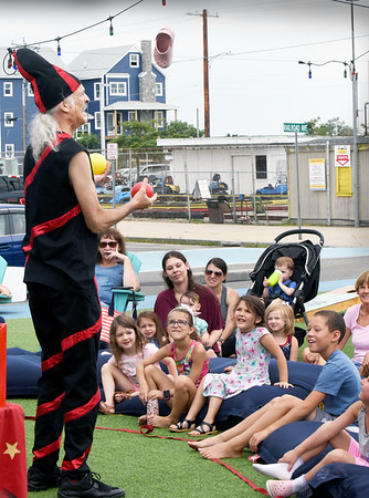BRYAN EATON/Staff Photo. Henry Lappen, a.k.a. Henry the Juggle performs for youngsters, grabbing one of their shoes into the mix with balls, at Salisbury Beach Tuesday morning. He was preceded by the Salisbury Public Library Story Time and Crafts with Thor the Therapy Dog during the weekly summertime shows.