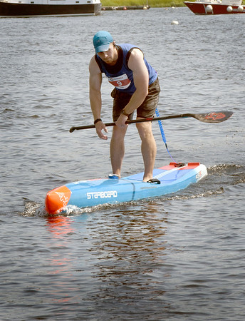 BRYAN EATON/Staff Photo. Rhodes Berube of Marblehead is the first SUP to cross the finish in the elite division.