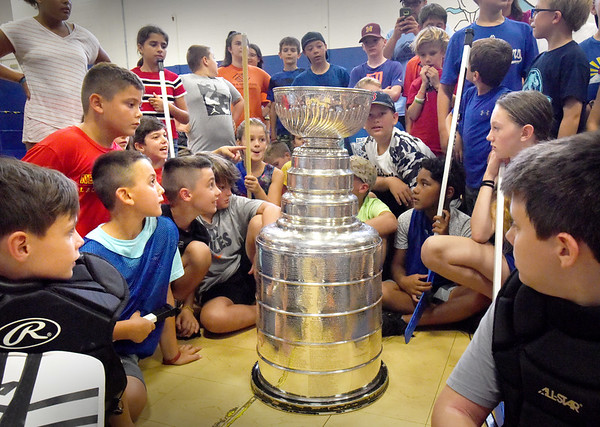 BRYAN EATON/Staff Photo. Youngsters at the Boys and Girls Club in Salisbury check out the Stanley Cup on Wednesday morning. The cup has been on tour and was brought to the club by Larry Pleau of Hampton, N.H. who is a former general manager of the St. Louis Blues who has volunteered at the club.