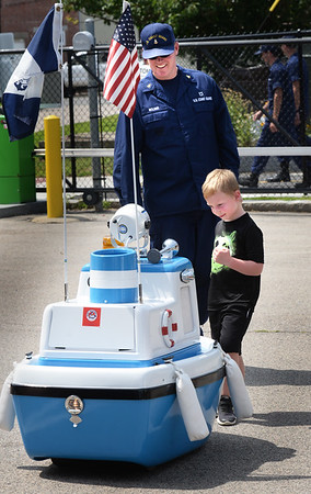 "BRYAN EATON/Staff Photo. Executive Petty Officer Ben Molnar looks on as Evan Hussey, 4, of Hampton, N.H. meets ""Coastie"" a talking boat the dispenses humor with water saftey tips at U.S. Coast Guard Station Merrimack during the open house."