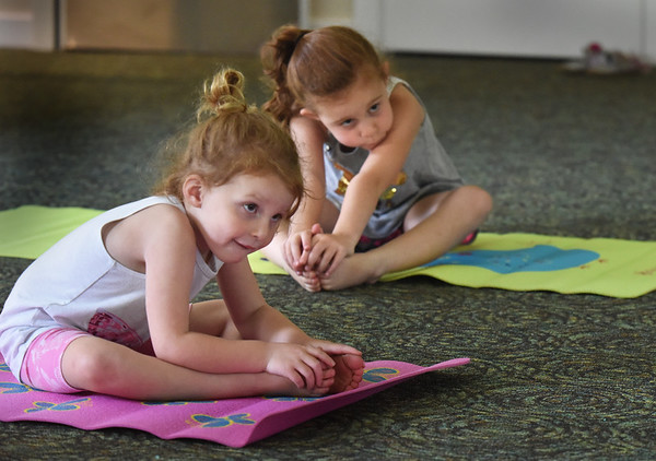 """BRYAN EATON/Staff Photo. Sisters Callie Herdman, 3, left, and Avery, 6, work on stretching and breathing excercises at the Salisbury Public Library. It was the fourth week of and eight week program """"Yoga For Kids"""" taught by Pat Stromquist."""