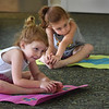 "BRYAN EATON/Staff Photo. Sisters Callie Herdman, 3, left, and Avery, 6, work on stretching and breathing excercises at the Salisbury Public Library. It was the fourth week of and eight week program ""Yoga For Kids"" taught by Pat Stromquist."