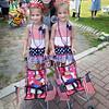 BRYAN EATON/Staff Photo. Yankee Homecoming General Chair poses with winners of the Most Patriotic Category, twins Jayla Peura, 5, left, and Joliene, of Rowley.