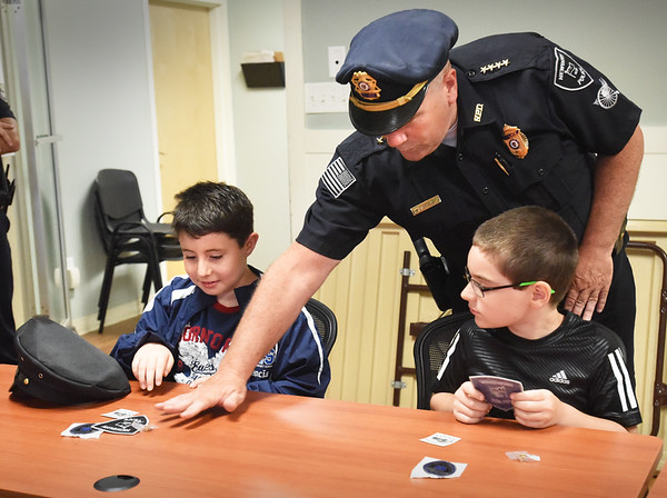 "BRYAN EATON/Staff Photo. Newbury Police Chief Michael Reilly gives some police decals to Ryan Mancia, left, and his friend Dalton Giusti, both 8, at the station on Tuesday afternoon. Ryan won a Newbury Elementary School PTA raffle to have ""Pizza With the Chief."""