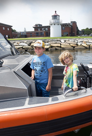 BRYAN EATON/Staff Photo. Jack Tramontana, 11, left, and his brother, Cooper, 5, of Newburyport pose for a photo on the response boat small during the U.S. Coast Guard Station Merrimack open house.