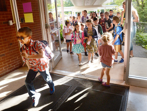 BRYAN EATON/Staff Photo. One enthusiastic youngster runs into the foyer of Amesbury Elementary School on Tuesday as classes started in the Amesbury school system. Triton and Pentucket return next Tuesday with Newburyport following that on Thursday.