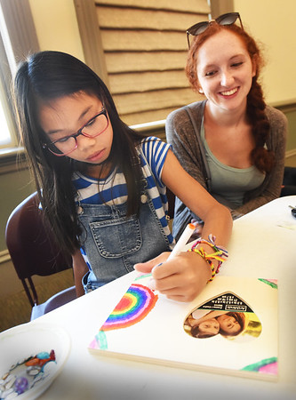 BRYAN EATON/Staff Photo. Phoebe Li Eyink, 10, with her sitter, Mariah Newman, attended a crafting event at the Newburyport Public Library on Tuesday morning. Children were given a picture frame with a heart shape cut-out for the photo, and they used coloring utensils and stickers to custom design theirs.