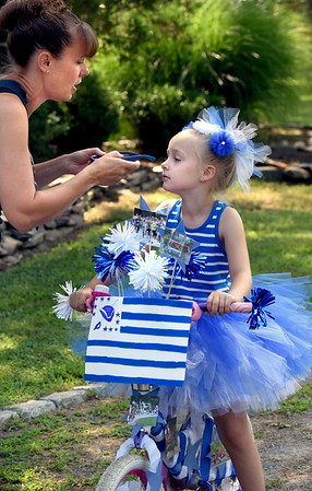 BRYAN EATON/Staff Photo. Meredith Bastine, originally from Newburyport, takes the sunglasses off her daughter, Lilly, 7, of Newton, N.H. before she started in the Kids Day in the Park Carriage and Bike Parade.