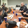 BRYAN EATON/Staff Photo. Ryan Mancia, left, and friend Dalton Giusti, both 8, have a pizza lunch with Newbury Police Chief and officers John Baker and Mark Smigielski at the station. Ryan won a Newbury Elementary School raffle for the privilege. After lunch Baker and Smigeilski took the boys to Plum Island to ride a police ATV on the beach.